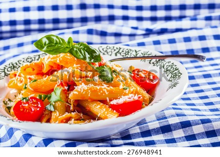 Plate with pasta pene Bolognese sauce cherry tomatoes parsley top and basil leaves on checkered blue tablecloth. Italian and Mediterranean cuisine  - stock photo