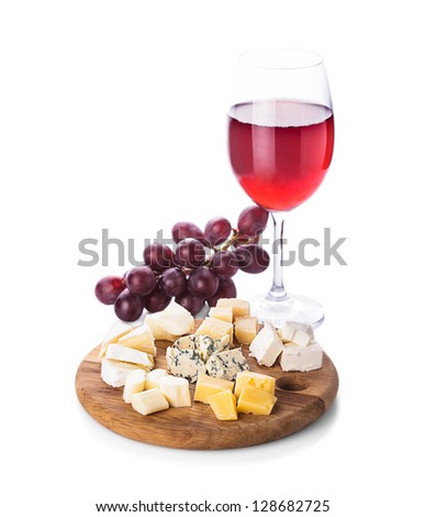 Plate with pieces of various types of cheese, grape and glass of wine, isolated on white - stock photo