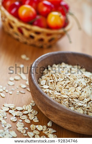 Plate with raw oatmeal and cherry on wooden table.