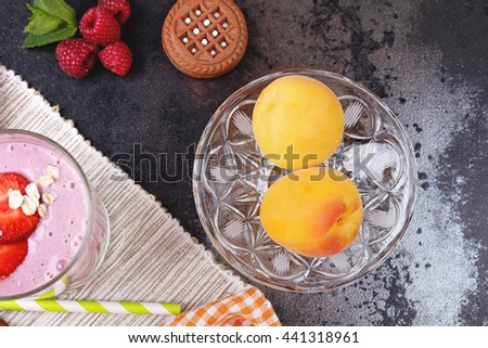 Plate with ripe apricots, chocolate chip cookies, raspberry, mint, straw berry yogurt smoothies and oatmeal flakes on the table. A delicious breakfast or lunch. Restaurant, cafeteria. - stock photo