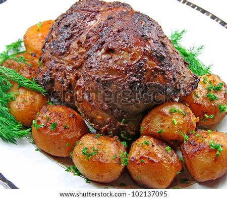Plate with roast leg of lamb, potatoes and dill - stock photo