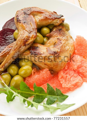 Plate with roasted rabbit legs and vegetable garnish. Shallow dof.