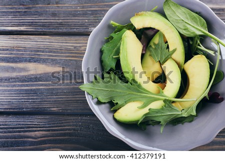 Plate with rocket and fresh avocado on wooden background - stock photo