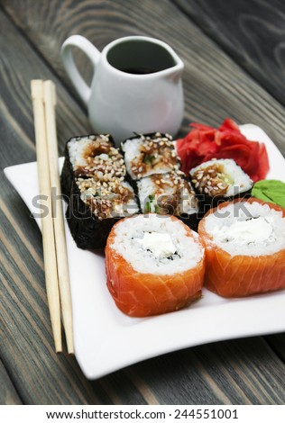 Plate with rolls, wasabi and ginger on a wooden background - stock photo