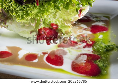 Plate with salad and strawberry olive dressing - stock photo