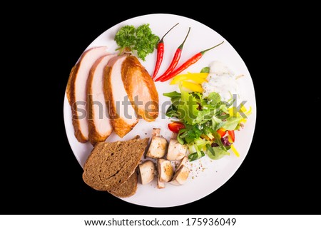 Plate with salad, fried mushrooms, chili pepper, bread and turkey isolated on black - stock photo