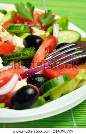 Plate with salad on green table - stock photo