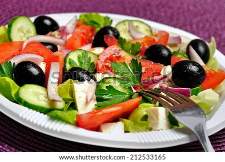 Plate with salad on purple table