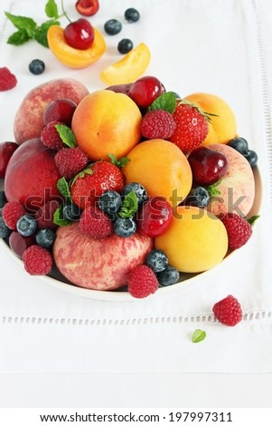 Plate with seasonal fruits and berries on white background. Close up.