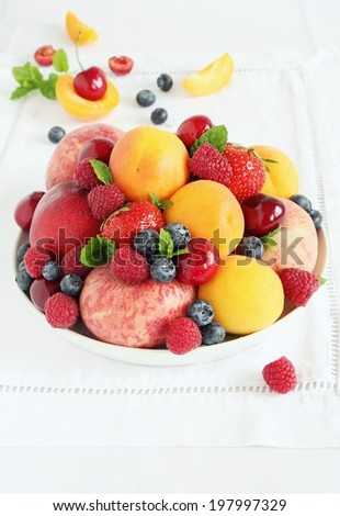 Plate with seasonal fruits and berries on white background. Close up. - stock photo