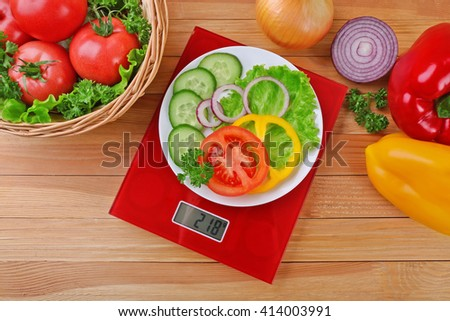 Plate with sliced fresh vegetables on digital kitchen scales over wooden background - stock photo