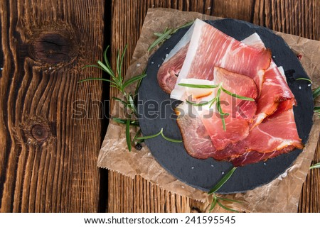 Plate with sliced Ham (close-up shot) on wooden background - stock photo