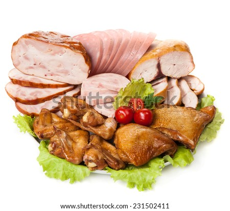 plate with slices of smoked chicken and chicken ham with greens and tomatoes - stock photo