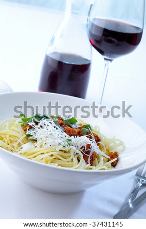 plate with Spaghetti Bolognese and red wine