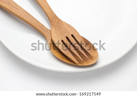 Plate with spoon and fork on white - stock photo