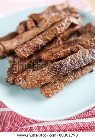 Plate with Strips of Sauteed Organic Grass Fed Beef - stock photo