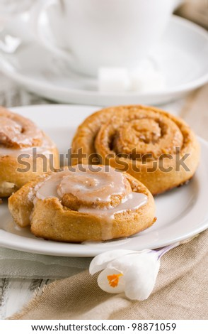 Plate with sweet cinnamon buns with white crocus flower