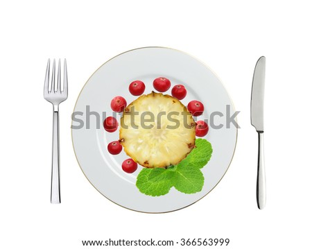 plate with sweet slice of pineapple, cranberry and mint herb, knife and fork isolated on white - stock photo