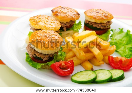 Plate with tasty mini burgers - stock photo