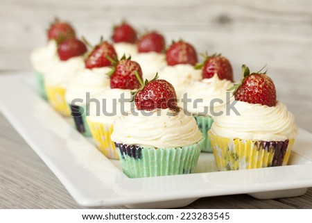 plate with ten cupcakes decorated with strawberries on wooden table - stock photo