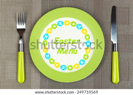"Plate with text ""Easter Menu"", fork and knife on tablecloth background - stock photo"