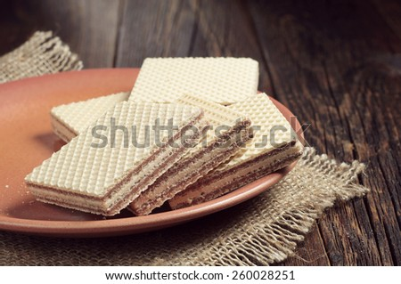 Plate with wafers on dark wooden table - stock photo
