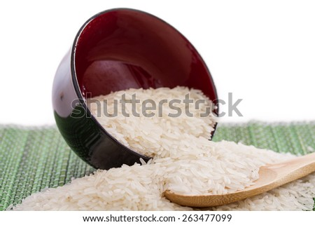 Plate with white rice and wooden spoon with white rice - stock photo