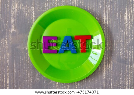 Plate with word EAT on the wooden background. Food concept.