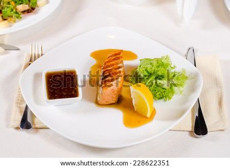 Plated Meal of Grilled Salmon with Sauce and Garnish Served in Restaurant - stock photo