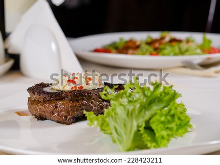 Plated Meal of Steak Topped with Herbed Butter and Garnish Served in Restaurant - stock photo