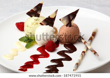 Plated scoops of gourmet flavored ice cream with pistachio, vanilla and chocolate decorated with drizzles of sauce and served with decorative chocolate wafers - stock photo
