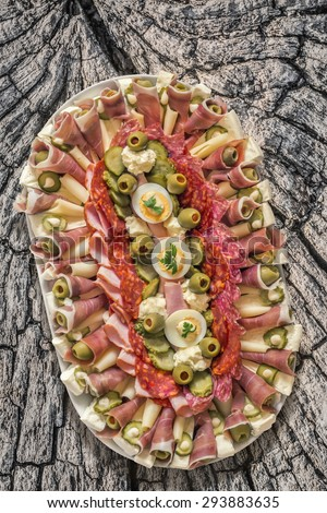 Plateful of Savoury Appetizer Meze, placed on very old, weathered, cracked, rotten Log Cross Section Surface. - stock photo