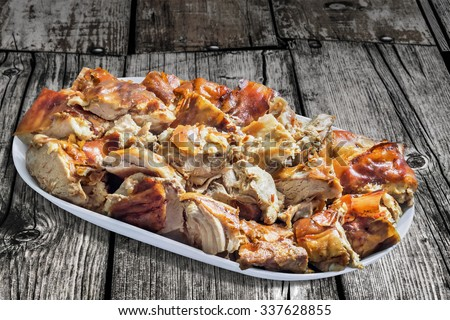 Plateful of Spit Roasted Pork Cut in Slices, on Old Wooden Floorboards Background. - stock photo