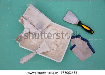 Platering tools for plaster like plaste trowel spatula on green drywall plasterboard - stock photo