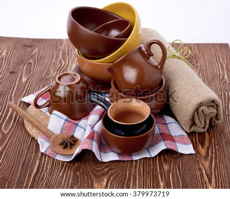 plates and cups on wooden table - stock photo