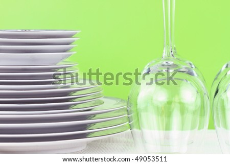 Plates and glasses against a green green background .