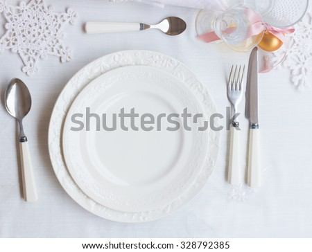 Plates and utensils on white tablecloth with christmas decorations - stock photo