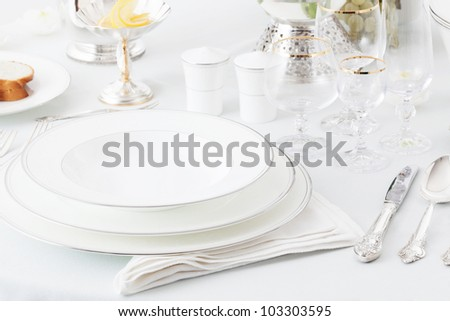 plates, glasses and silverware on the holiday table - stock photo
