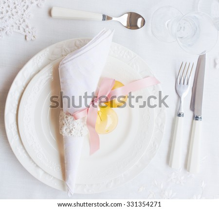 Plates, napkin and utensils on white tablecloth with christmas decorations - stock photo