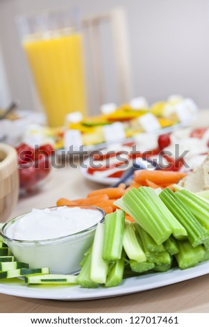 Plates of fresh celery, cucumber dip & salad on a table with tomato and mozzarella prepared for a healthy dinner party. - stock photo