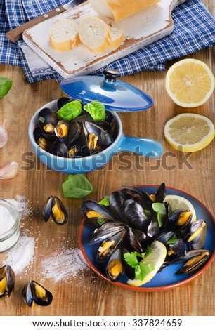 Plates of steamed mussels on a wooden background. View from above - stock photo