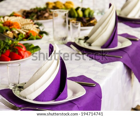 plates on table waiting for guests. focus on front plate - stock photo