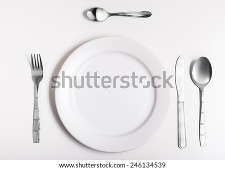 Plates with a silver fork, spoon, dessert spoon and a knife isolated on white