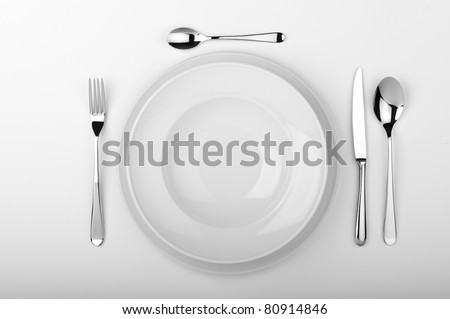 Plates with a silver fork, spoon, dessert spoon and a knife isolated on white studio background