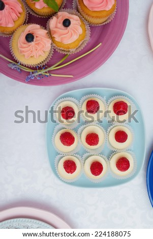 plates with cupcakes decorated with strawberries and cream on the table - stock photo