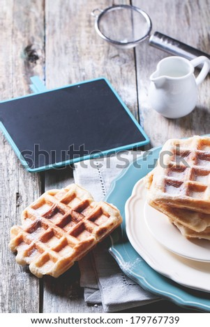 Plates with fresh belgian waffles served with empty black chalkboard over old wooden table. See series - stock photo