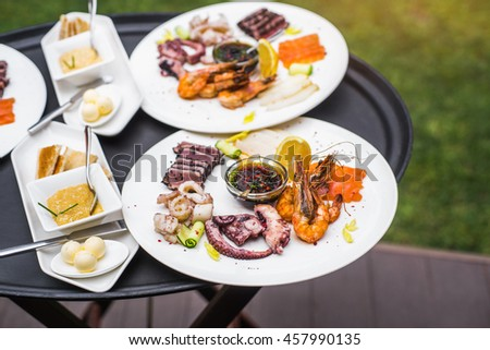 Plates with seafood mix, food snacks on an event party, wedding, birthday or dinner