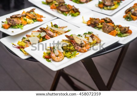 Plates with seafood mix, salad, food snacks on an event party, wedding, birthday or dinner