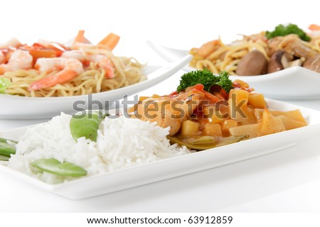Plates with tasty oriental food on reflective surface. Focus on the plate with rice, chicken meat and vegetables. Studio shot. White background.