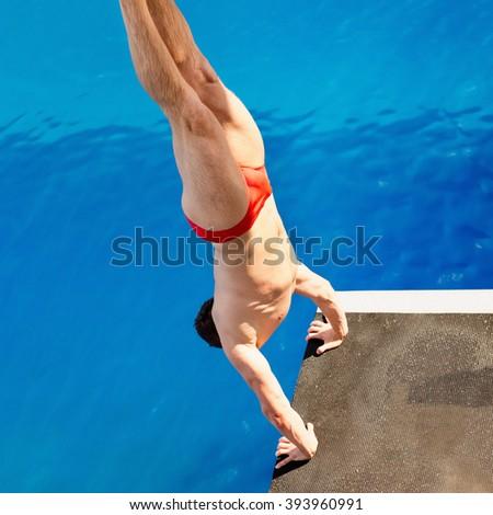 Platform diver, starting from handstand - stock photo
